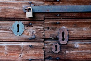 Old wooden door with four locks cover by rust