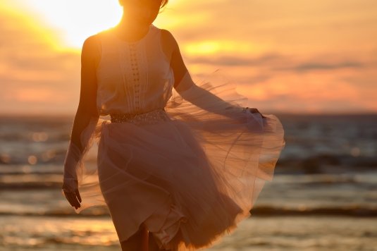 The silhouette of a slim girl in lush pink short skirt, standing on the sand against the sea and the Golden sunset